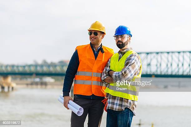 Engineers with blueprints at the construction site near river