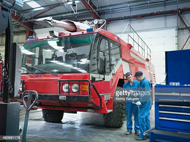 Engineers with fire engine in truck repair factory