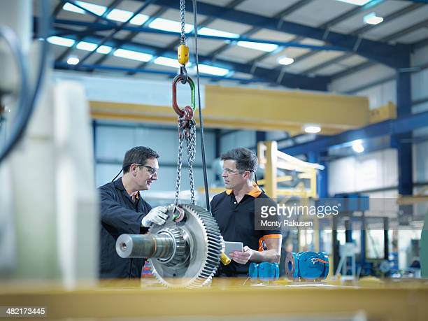 Engineers with gear wheel at work station in factory