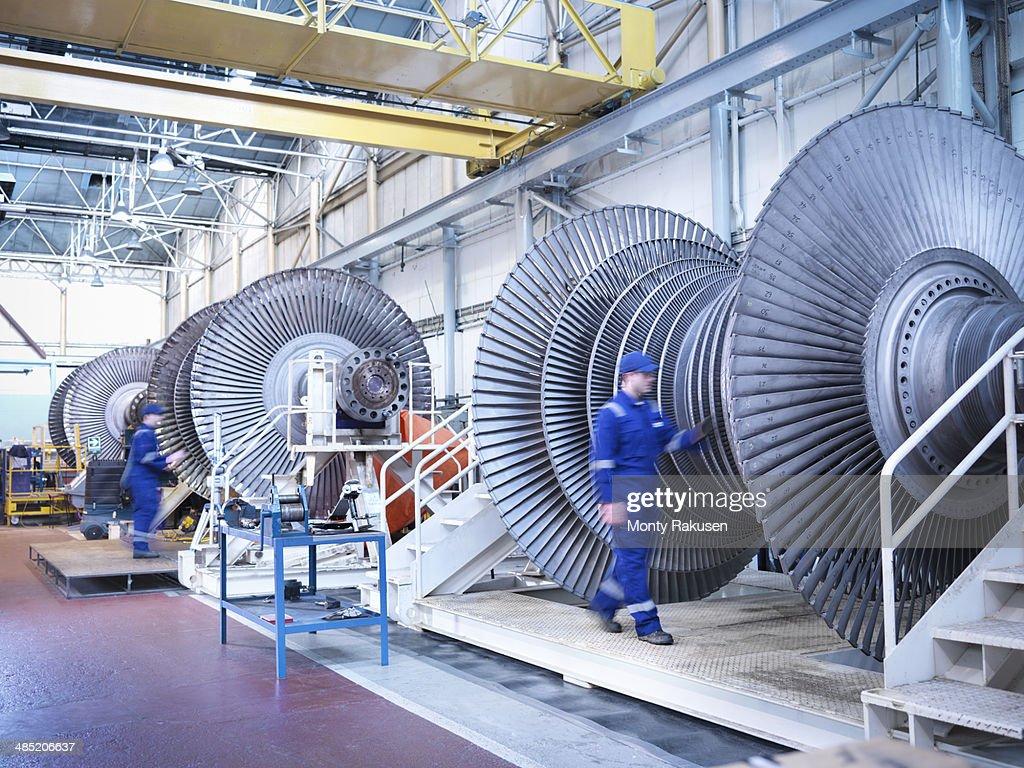 Engineers with low pressure steam turbines in repair bays in workshop
