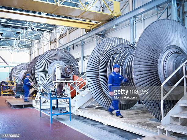 Engineers with low pressure steam turbines in repair bays in workshop