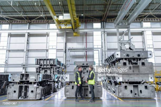 Engineers with steel pressing moulds in car factory