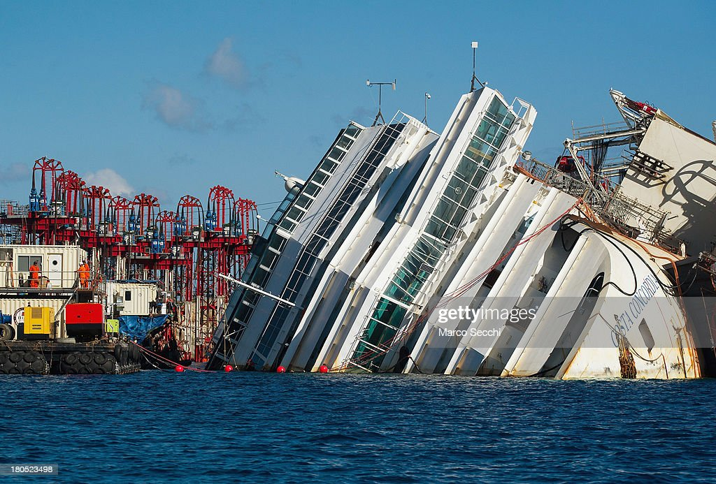 Engineers work near the wreckage of the Costa Concordia on September 14, 2013 in Isola del Giglio, Italy. The Costa Concordia is reportedly due to be righted beginning on the morning of September 16, then, if the operation is successful, it will be towed away and scrapped.