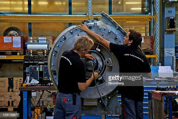 Engineers work on the assembly of a turbocharging unit at the ABB Turbo Systems plant operated by ABB AG in Baden Switzerland on Tuesday Aug 30 2011...