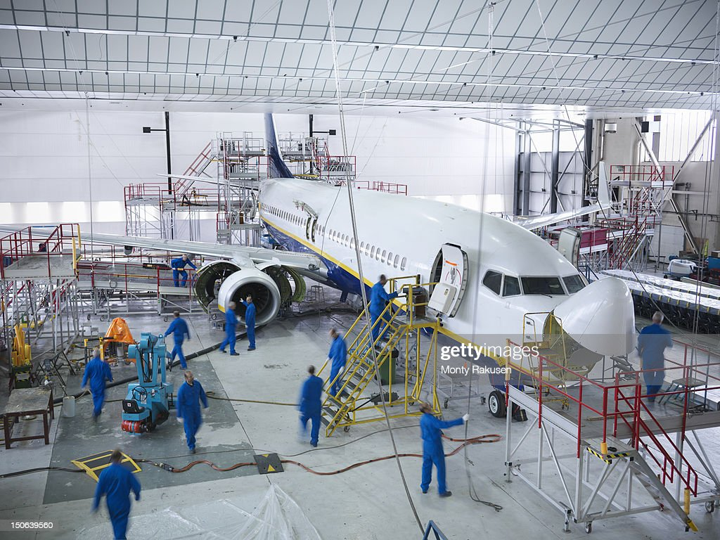 Engineers working with aircraft in repair hangar : Stock Photo