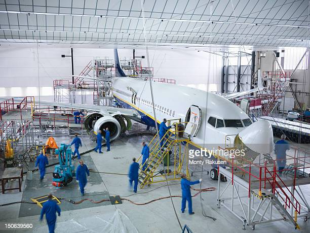 Engineers working with aircraft in repair hangar