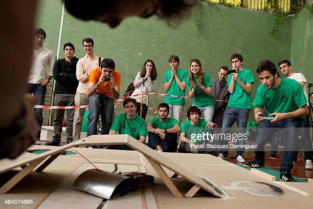 Enginnering student Carlos Hucha competes with his robot 'Troncomovil' at a sumo robots combat while other students react during the Cybertech...
