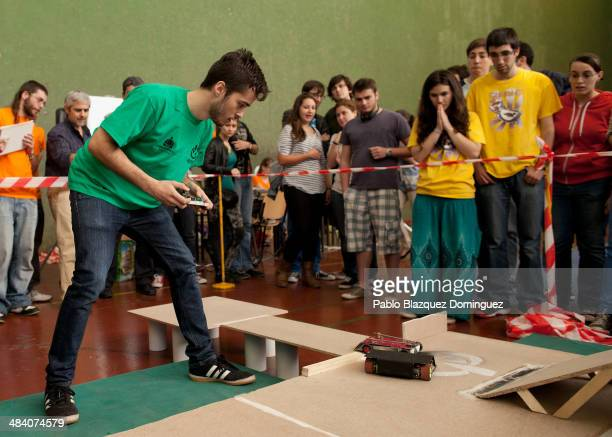 Enginnering student Carlos Hucha competes with his robot 'Troncomovil' at a sumo robots combat while other students look during the Cybertech...
