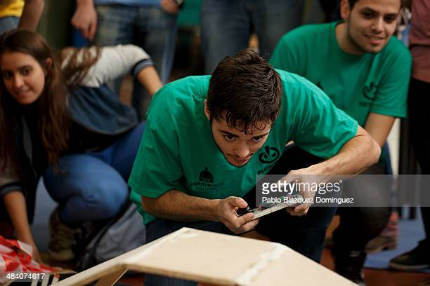 Enginnering student Carlos Hucha competes with his robot 'Troncomovil' at a sumo robots combat during the Cybertech robotics competition at the the...