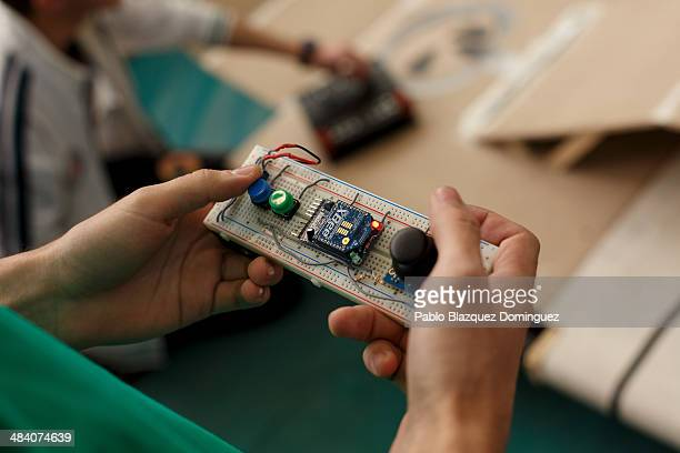 Enginnering student Carlos Hucha holds the remote control of his robot 'Troncomovil' before a sumo robots combat during the Cybertech robotics...