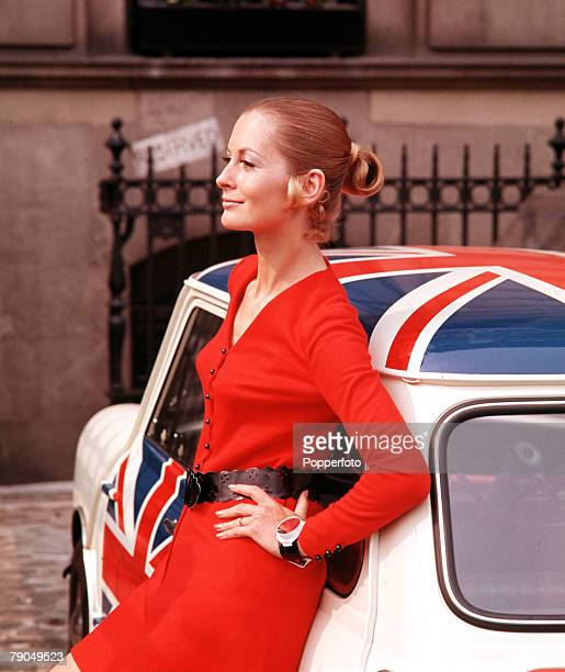 England A model wearing a red dress with black belt is pictured leaning on a Mini motor car complete with Union Jacks on its roof and side