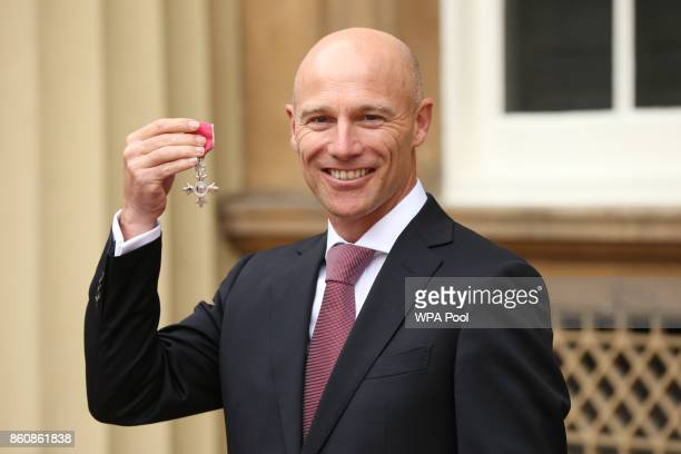 England and Great Britain hockey head coach Danny Kerry is made an MBE by Queen Elizabeth II during an Investiture ceremony at Buckingham Palace on...