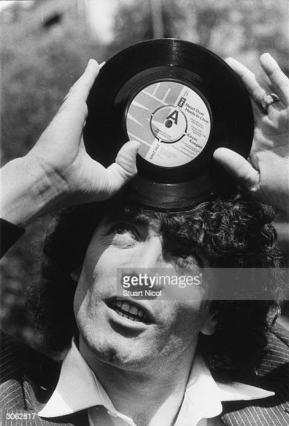England and SV Hamburg footballer Kevin Keegan holding a demo copy of his latest single 'Head Over Heels In Love'