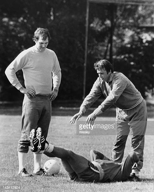 England assistant manager Geoff Hurst stretches the legs of player Tony Currie as his teammate Joe Corrigan looks on during a training session at...