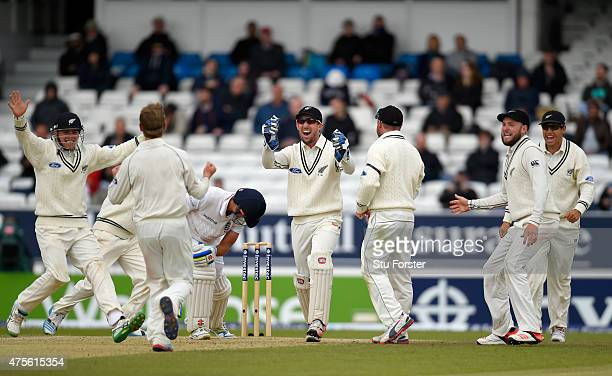 England batsman Alastair Cook prods forward as wicketkeeper Luke Ronchi and bowler Kane Williamson and fielders celebrate after dismissing him lbw...