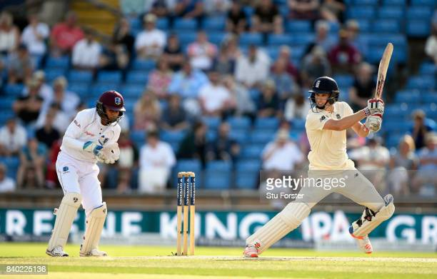 England batsman Chris Woakes cuts a ball towards the boundary watched by keeper Shane Dowrich during day four of the 2nd Investec Test Match between...