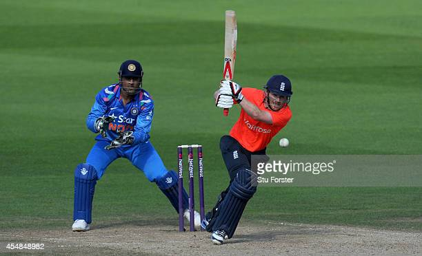 England batsman Eoin Morgan hits out watched by MS Dhoni during the NatWest T20 International between England and India at Edgbaston on September 7...