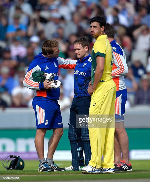 England batsman Eoin Morgan is looked at by the physio after being hit on the helmet by a ball from Mitchell Starc and retires hurt during the 5th...