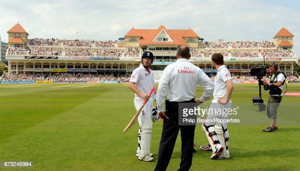 England batsman Ian Bell and Eoin Morgan speak to umpire Tim Robinson as they wait for a run out decision during the 2nd Test match against India at...