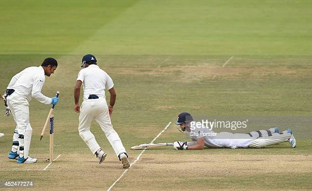 England batsman James Aanderson lies stranded after being run out as India captain MS Dhoni picks out a stump as India win the test match during day...