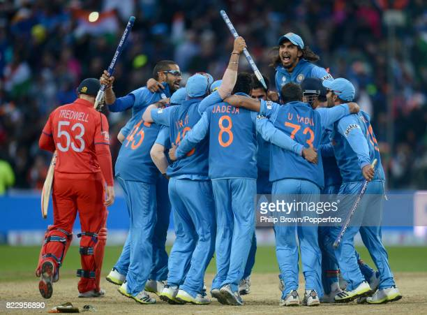 England batsman James Tredwell trudges off the field as the India team including Shikhar Dhawan and Ishant Sharma celebrate winning the ICC Champions...