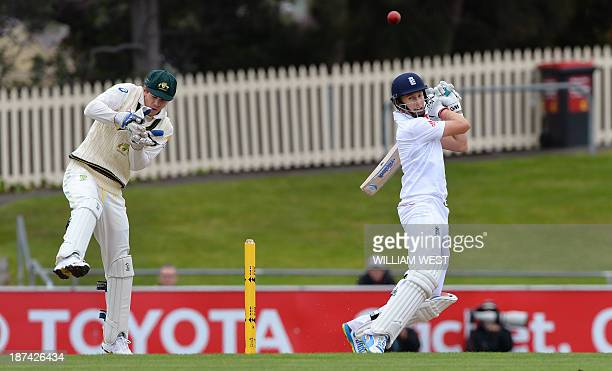 England batsman Joe Root cuts a ball away as Australia A wicketkeeper Tim Paine looks on the final day of their cricket match played at the Bellerive...