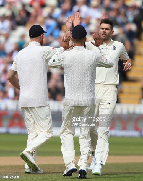 England bowler James Anderson celebrates with teammates after taking the wicket of West Indies' Kyle Hope during play on day 3 of the first Test...