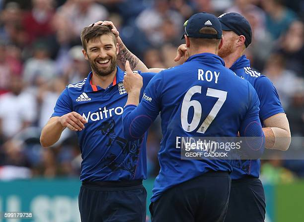 England bowler Mark Wood celebrates with England's Ben Stokes and England's Jason Roy after taking the wicket of Pakistan's Babar Azam during play in...