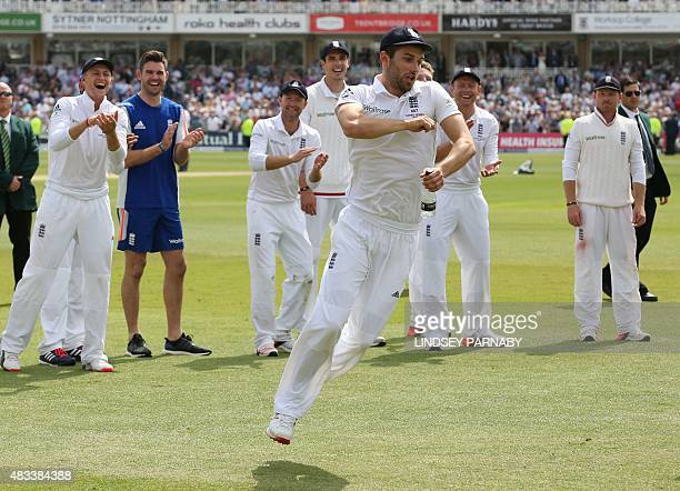 England bowler Mark Wood celebrates with teammates on the pitch after England wrap up the game and retain the Ashes on the third day of the fourth...