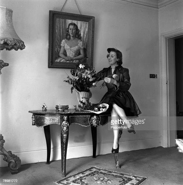 1952 England British singer Vera Lynn arranges flowers at a table in her home