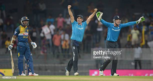 England captain Alastair Cook and Jos Buttler celebrate the wicket of Kumar Sangakkara of Sri Lanka during the 1st One Day International between Sri...