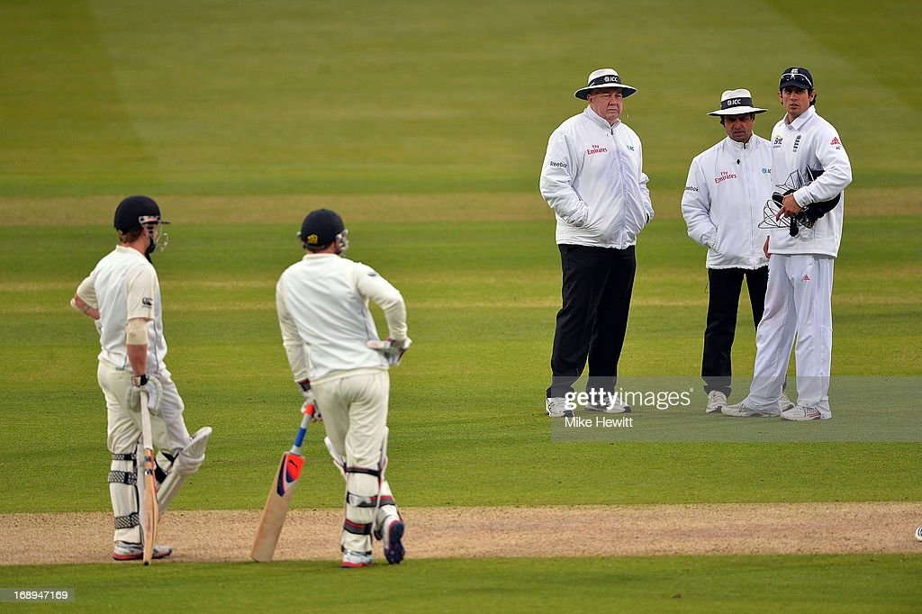 England captain <a gi-track='captionPersonalityLinkClicked' href=/galleries/search?phrase=Alastair+Cook+-+Cricket+Player&family=editorial&specificpeople=571475 ng-click='$event.stopPropagation()'>Alastair Cook</a> (R) discusses the light with umpires Steve Davis and Aleem Dar at the end of day two of 1st Investec Test match between England and New Zealand at Lord's Cricket Ground on May 17, 2013 in London, England.
