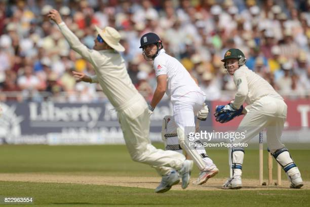 England captain Alastair Cook is caught by Australia's Michael Clarke for 50 runs as wicketkeeper Brad Haddin looks on during the 1st Test match...