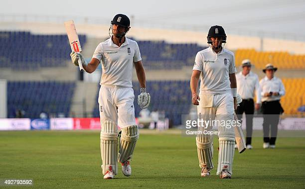 England captain Alastair Cook leaves the field alongside Joe Root at stumps on day three of the 1st Test between Pakistan and England at Zayed...
