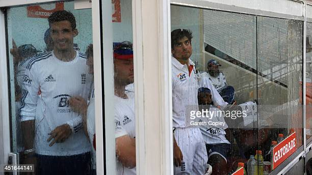 England captain Alastair Cook looks out of the dressing room window as rain stops play during day four of the First Ashes Test match between...
