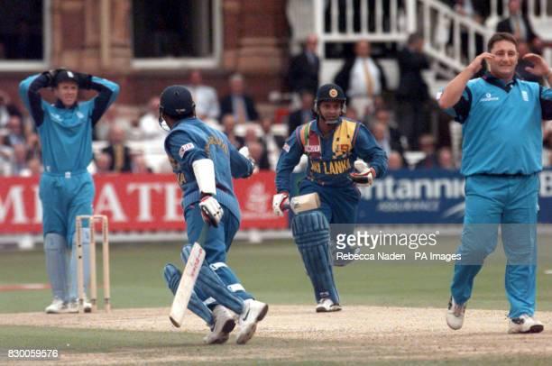 England captain Alec Stewart watches with bowler Ian Austin as Sri Lanka's Marvan Atapattu and captain Arjuna Ranatunga complete another run during...