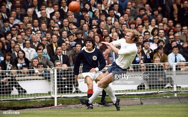 England captain Bobby Moore challenges Scotland player Peter Cormack during a Home International Championships match between England and Scotland at...
