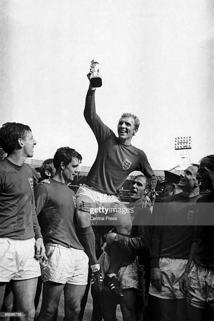 England captain Bobby Moore (1941 - 1993) holds aloft the Jules Rimet World Cup trophy as he sits on the shoulders of teammates Geoff Hurst and Ray Wilson after the World Cup Final match at Wembley, 30th July 1966.