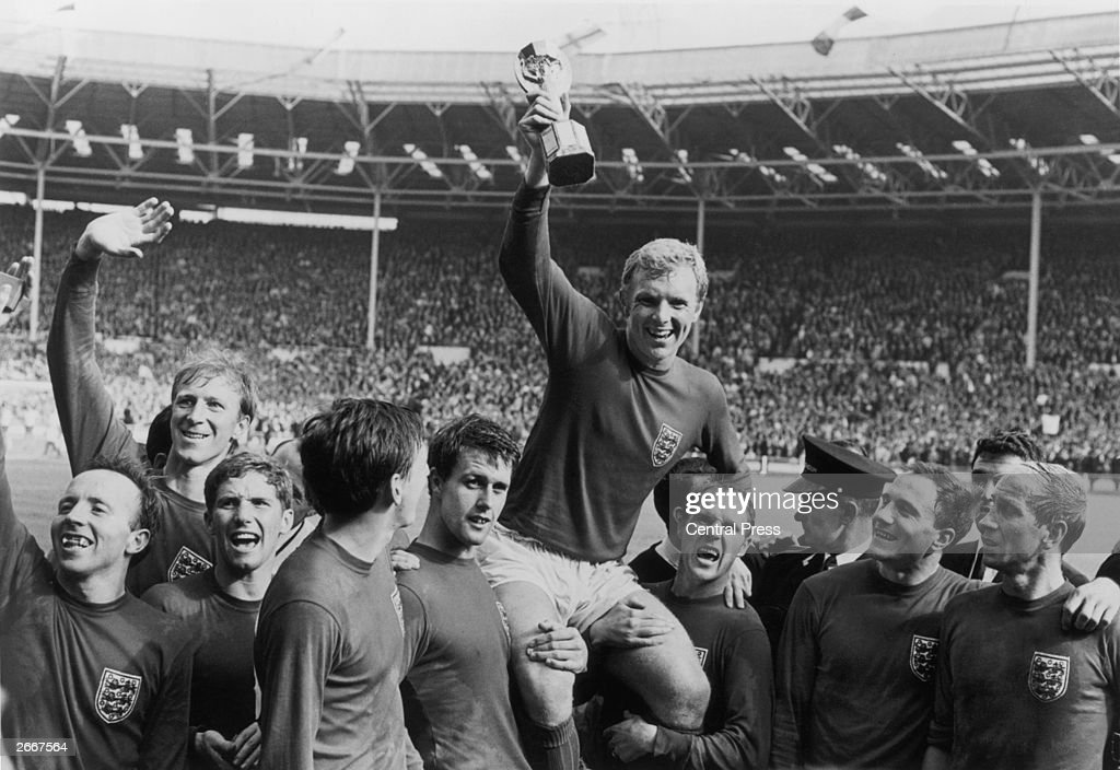 England captain <a gi-track='captionPersonalityLinkClicked' href=/galleries/search?phrase=Bobby+Moore&family=editorial&specificpeople=206646 ng-click='$event.stopPropagation()'>Bobby Moore</a> (1941 - 1993) holds up the Jules Rimet trophy as he is carried on the shoulders of his team-mates after their 4-2 victory over West Germany in the World Cup Final at Wembley Stadium. Also pictured are (left-right) Nobby Stiles, Jack Charlton, <a gi-track='captionPersonalityLinkClicked' href=/galleries/search?phrase=Alan+Ball+-+World+Cup+Winner&family=editorial&specificpeople=213401 ng-click='$event.stopPropagation()'>Alan Ball</a>, Martin Peters, Geoff Hurst, Ray Wilson, George Cohen and Bobby Charlton.