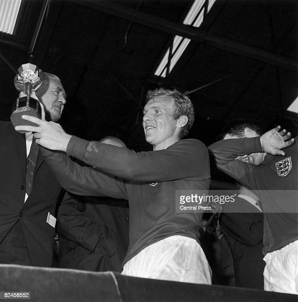 England captain Bobby Moore holds up the World Cup trophy after beating West Germany 42 at Wembley 30th July 1966 Geoff Hurst who scored a hattrick...
