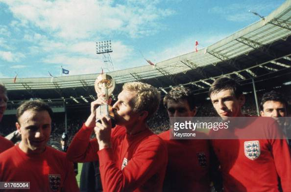 England captain Bobby Moore kissing the Jules Rimet trophy as the team celebrate winning the 1966 World Cup final against Germany at Wembley Stadium...