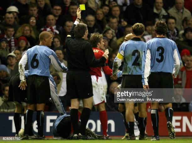 England captain David Beckham is booked by referee Stefano Farina during the friendly International match against Uruguay at Anfield Liverpool...