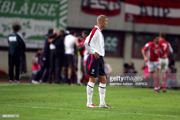 England captain David Beckham stands dejected as the Austria team celebrate equalizing