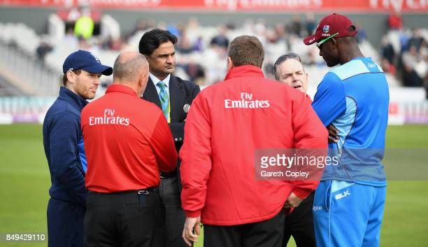 England captain Eoin Morgan and West Indies captain Jason Holder speak to match officials as the start is delayed ahead of the 1st Royal London One...