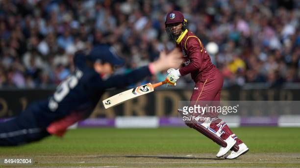 England captain Eoin Morgan dives in vain to stop a shot from West Indies batsman Evin Lewis during the 1st Royal London One Day International match...
