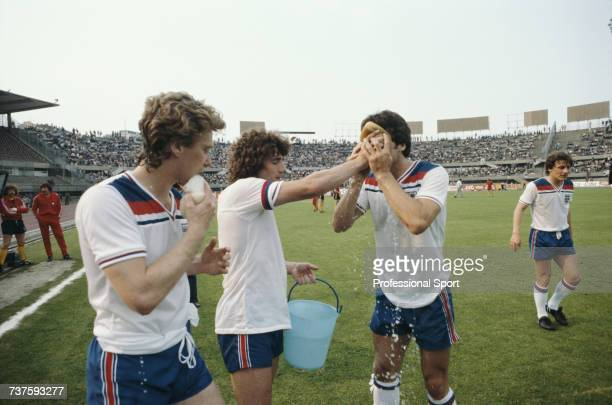 England captain Kevin Keegan holds a bucket of water as he offers sponges to team mates Tony Woodcock and David Johnson with midfielder Steve Coppell...