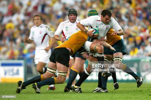England captain Martin Johnson charges through the tackles of Australia's Justin Harrison and David Lyons during the Rugby World Cup Final at the...