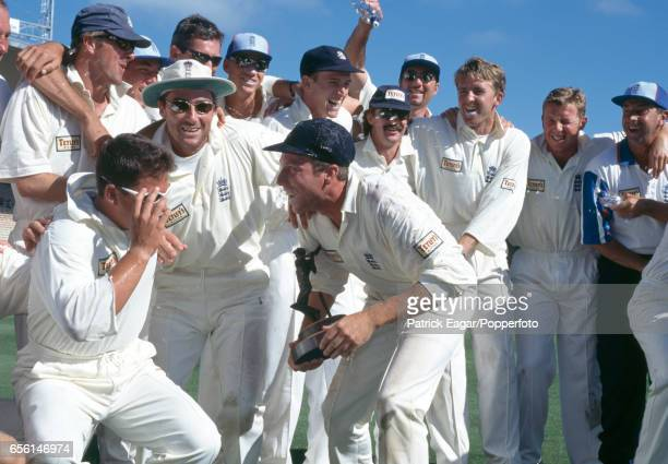 England captain Mike Atherton holding the series trophy is squirted with water during the presentation ceremony after England won the 3rd Test match...