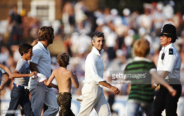 England captain Mike Brearley and Ian Botham leave the field as spectators rush on during the 6th and final test match between England and Australia...