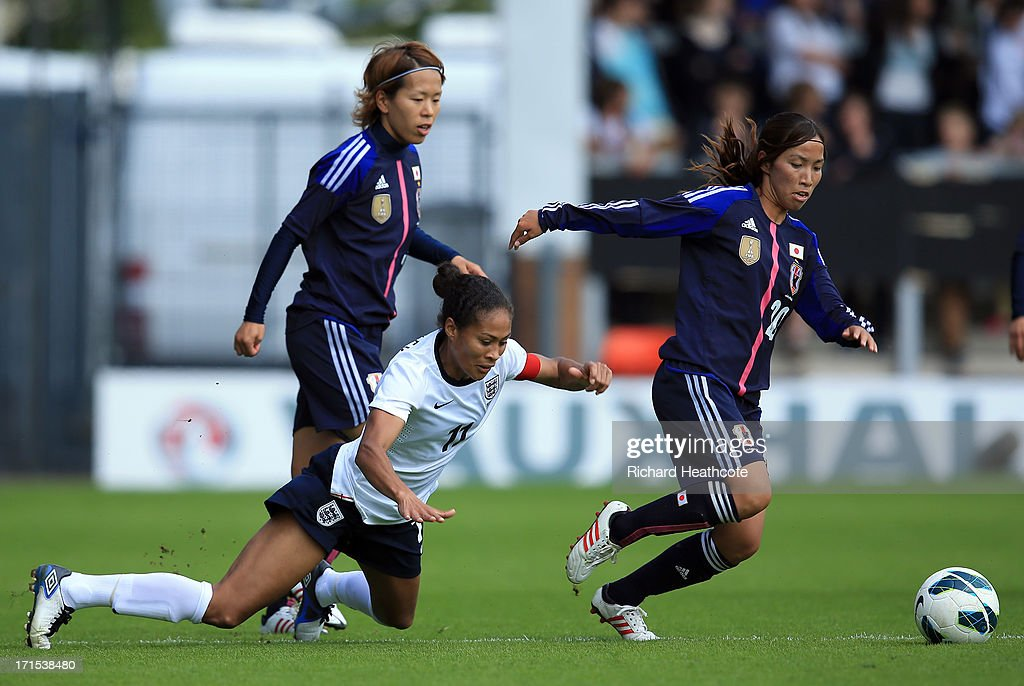 England captain Rachel Yankey is tackled by Emi Nakajima of Japan during the Women's International match between England and Japan at the Pirelli Stadium on June 26, 2013 in Burton-upon-Trent, England.